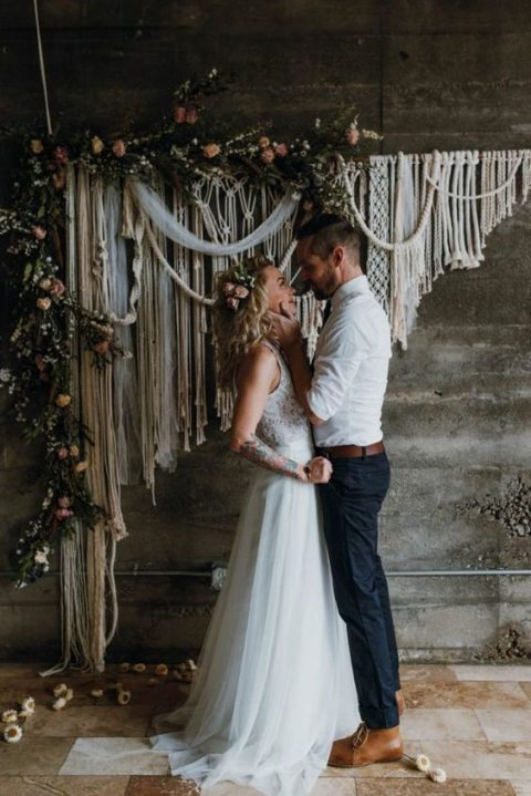 a macrame wedding backdrop with greenery and blush blooms