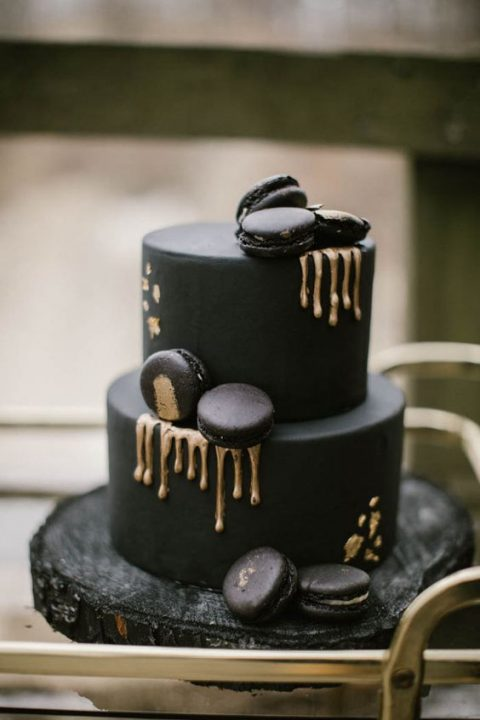 a matte black wedding cake with gold dripping_ gold leaf and macarons on top for a moody wedding
