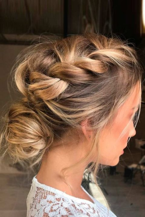 a messy braided updo with a low bun and some locks down