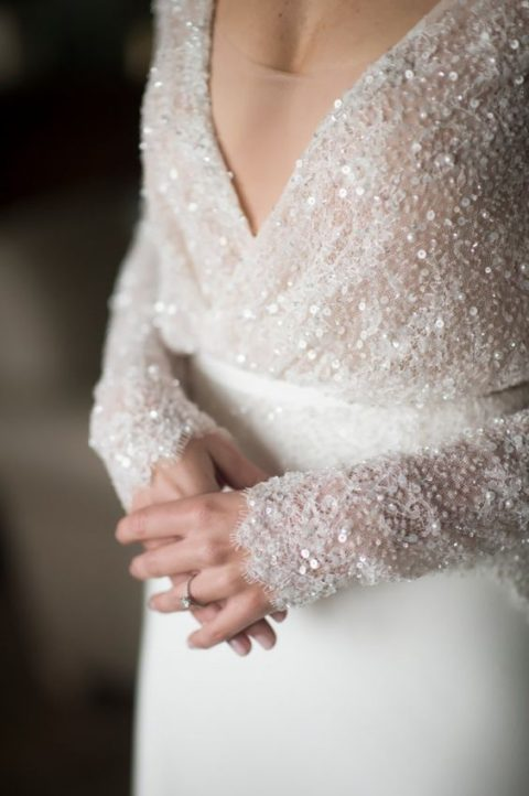 a modern wedding dress with a sequined bodice_ long sleeves_ a plain skirt and a covered neckline