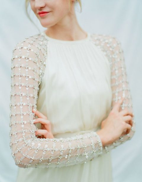a modern wedding gown with embellished sleeves will keep you warm and stylish at the same time