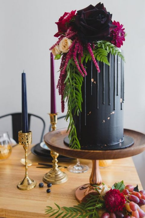 a moody tall wedding cake with gold leaf_ lush blooms and greenery