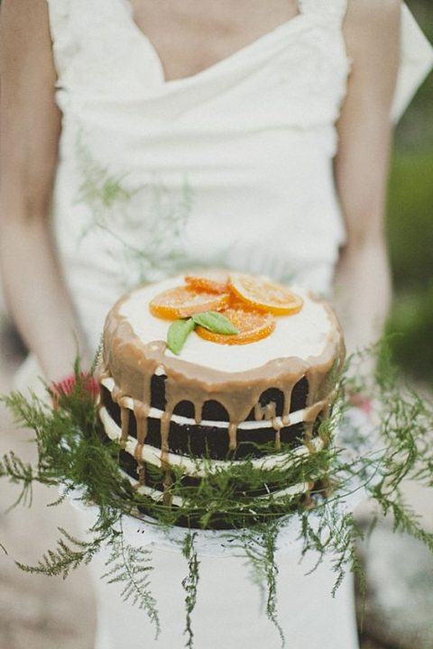 a naked chocolate wedding cake with caramel drip_ candied citrus and greenery