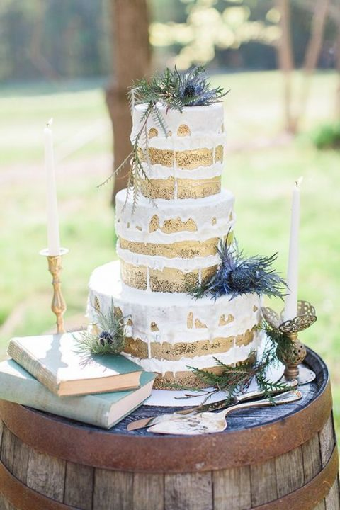 a naked wedding cake with drip and thistles looks cool and tasty