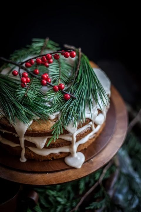 a naked wedding cake with white dripping_ evergreens and cranberries for a relaxed Christmas wedding