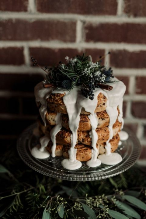 a non-traditional wedding cake covered with frosting_ thistles_ cinnamon sticks and evergreens