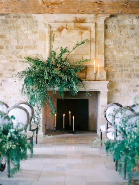 a non-working fireplace with candles and lush greenery
