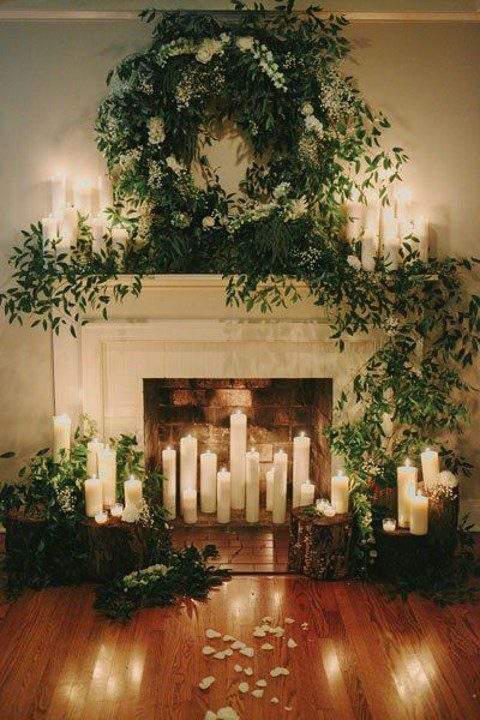 a non-working fireplace with lots of greenery and candles for a romantic ceremony
