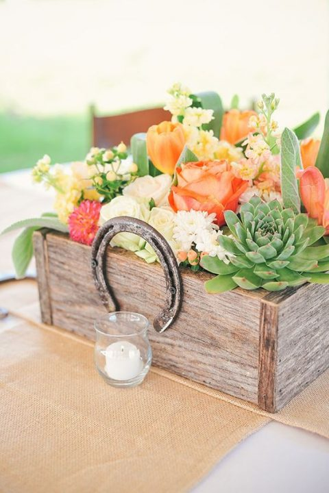a reclaimed wooden box with bold florals and succulents topped with a horse shoe