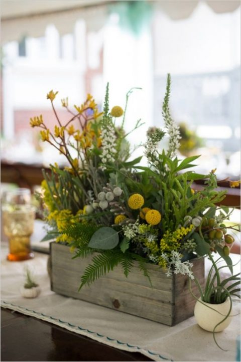 a reclaimed wooden box with textural greenery, billy balls and flowers