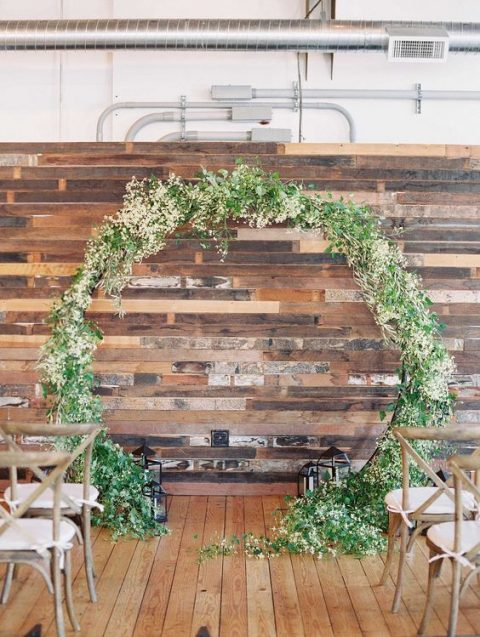 a reclaimed wooden wall and a circle wedding arch covered with greenery and blooms
