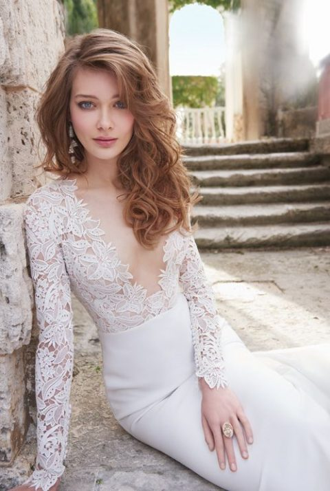 a stunning wedding dress with long sleeves and a lace bodice with a plunging neckline_ a plain skirt