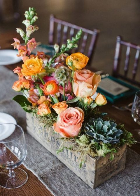 a vintage box with moss and orange and pink flowers