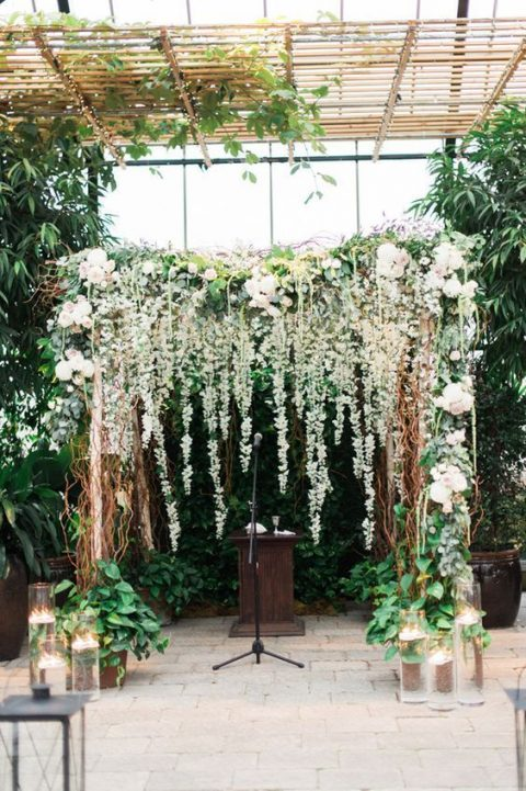 a wedding arch with lush greenery and flowers and candles around