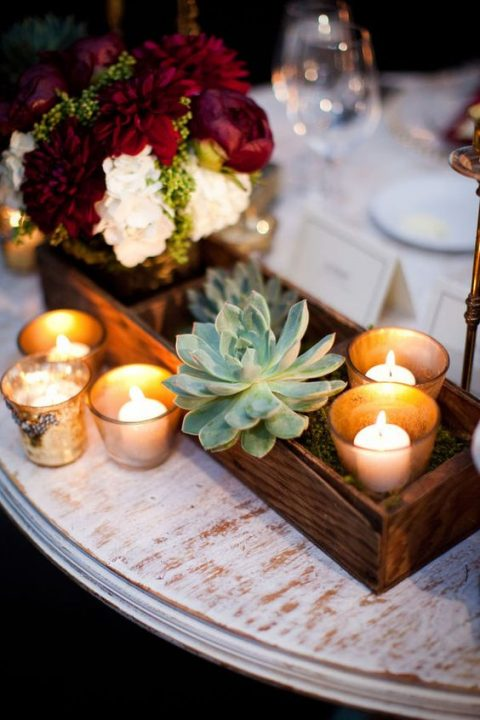 a wooden box with blooms in a jar, candles and succulents