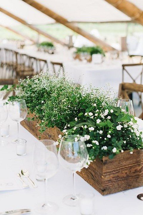a wooden box with lots of greenery and white flowers