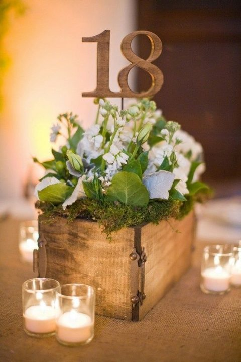 a wooden box with moss, greenery and blooms