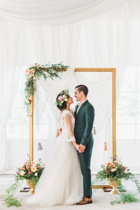 an airy fabric backdrop_ an oversized picture frame decorated with greenery and flowers