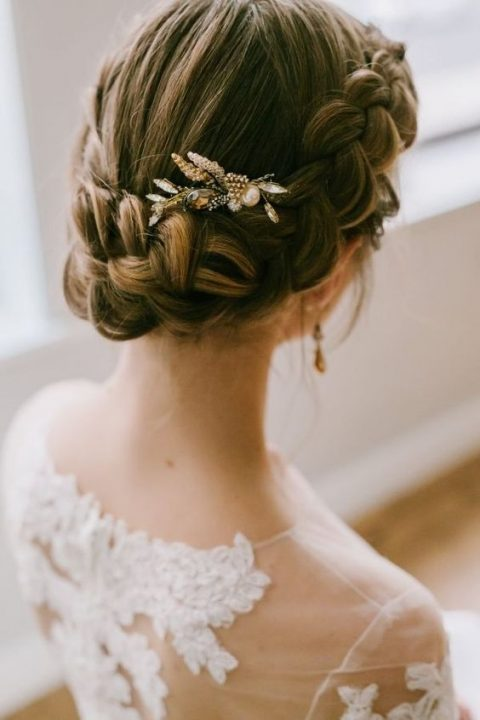 an elegant braided updo with a pearl and amber hairpiece