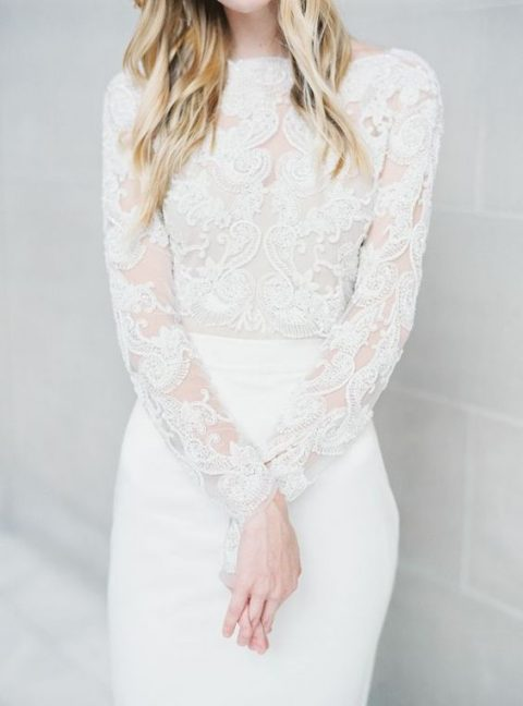 an ethereal wedding dress with a lace bodice with long sleeves_ a high neckline and a sleek skirt