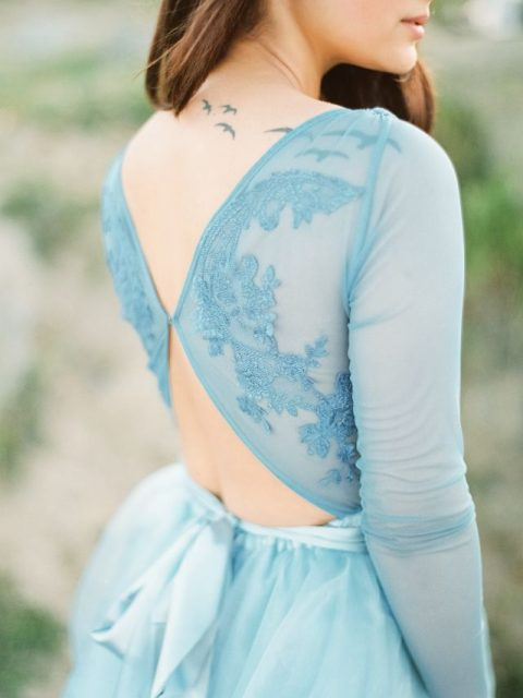 an ice blue wedding dress with an illusion lace top with back cutouts and a flowy skirt