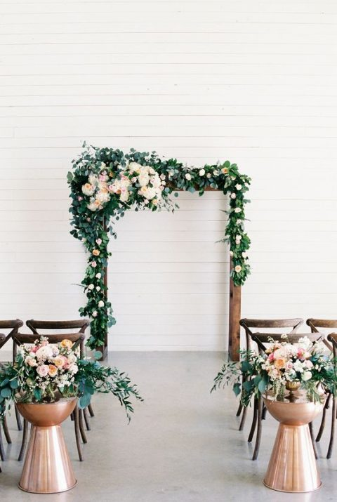 an indoor wedding arch with greenery and lush blooms can be taken outdoors