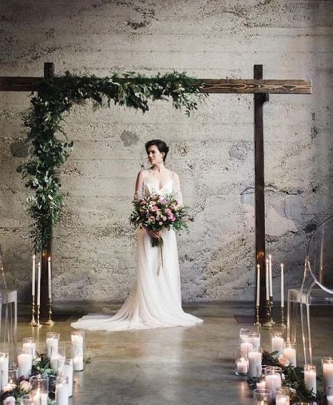 an indoor wood arch with greenery and lots of candles for the aisle