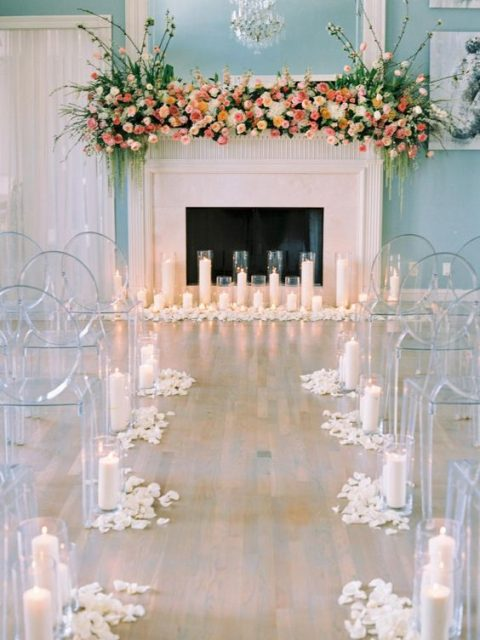 faux fireplace lushly decorated with various blooms_ greenery and lined up with candles