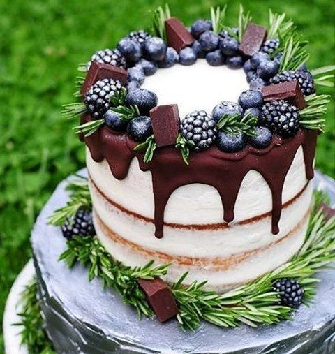 semi naked wedding cake with chocolate drip_ blueberries_ blackberries_ chocolate pieces