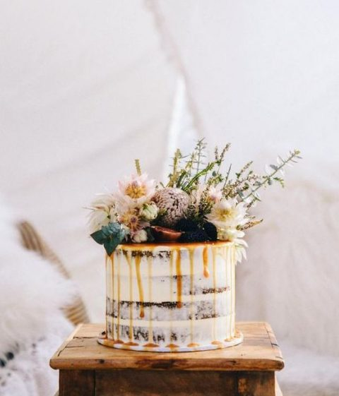 semi-naked wedding cake with lush neutral blooms_ herbs and cramel drip