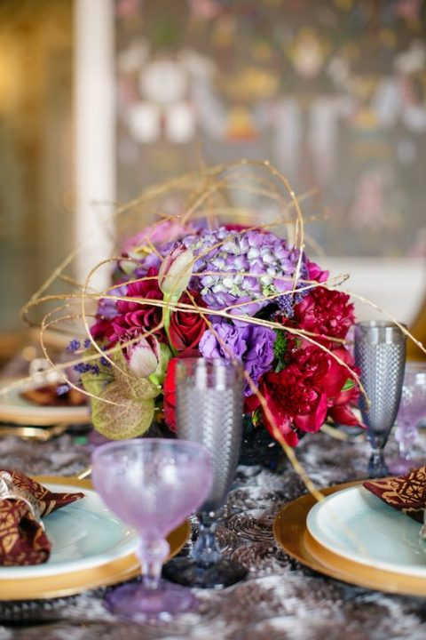a bold floral centerpiece in deep red and violet with gold touches