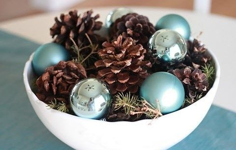 a bowl with pinecones, evergreens and turquoise ornaments