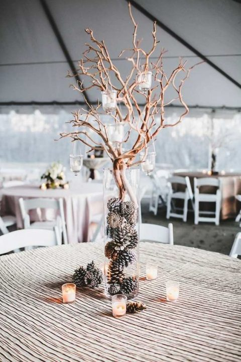 a glass vase with pinecones, branches and candle holders hanging