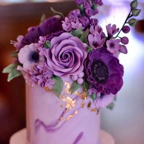 a lilac wedding cake with gold leaf and violet and deep purple flowers on top