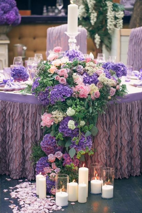 a lush tablescape with a lilac ruffled tablecloth and pink, white and violet blooms that cascade down the table