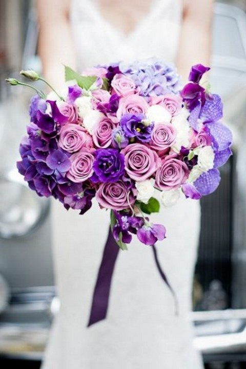 a lush wedding bouquet with violet, purple, pink and white blooms