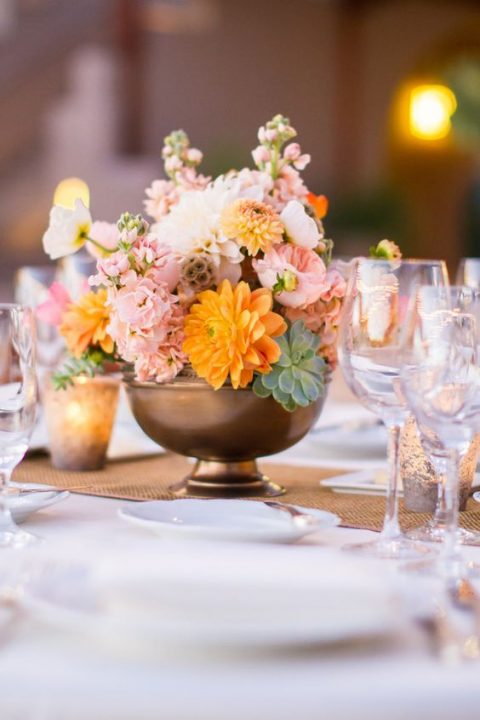 a metallic bowl with pink and orange blooms and succulents