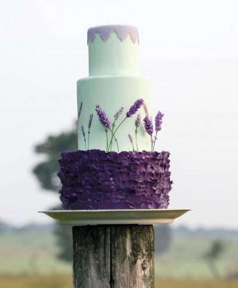 a mint wedding cake with a lavender top and a ruffled violet layer with lavender