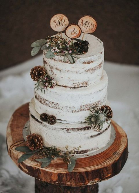 a semi naked wedding cake with thistles, greenery and pinecones