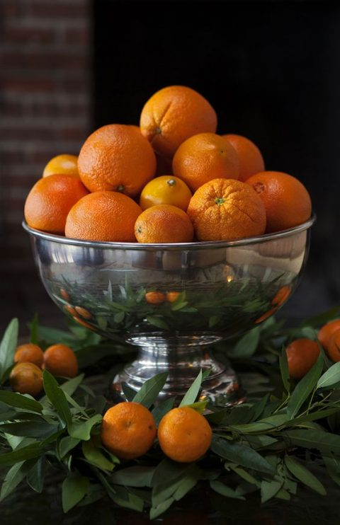 a silver bowl with oranges and tangerins