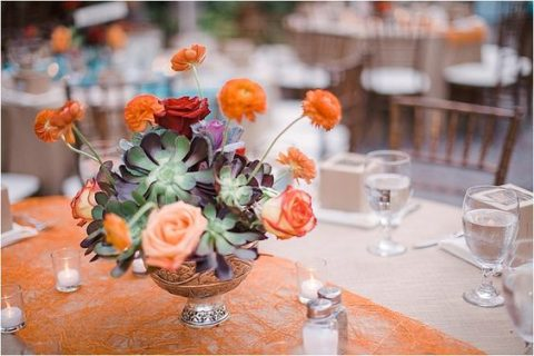 a silver bowl with succulents and bold orange blooms