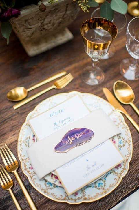 a small violet geode slice with gilded touches as a place card