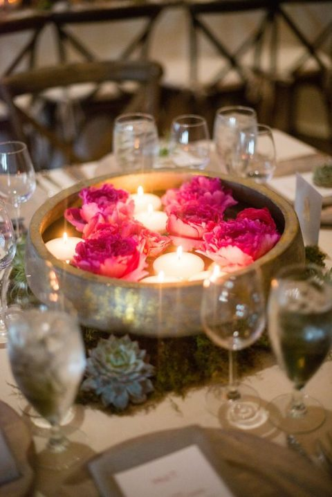 a stone bowl with floating blooms and candles