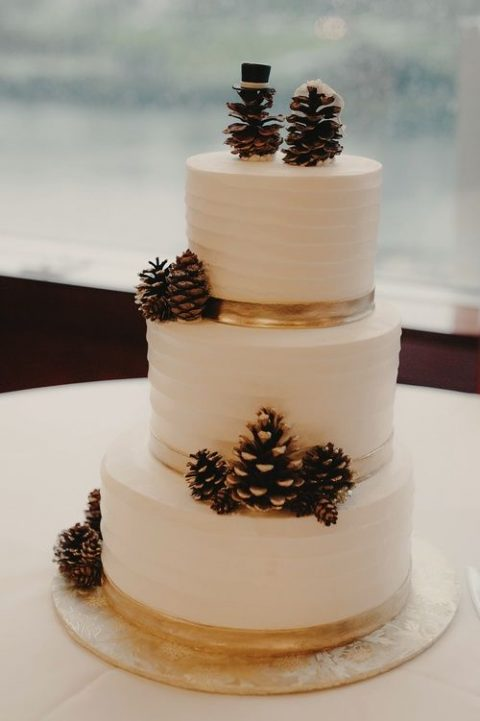 a textural white wedding cake with pinecones and pinecone toppers