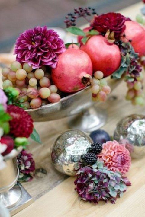 a vintage silver bowl with fresh fruits and bold blooms