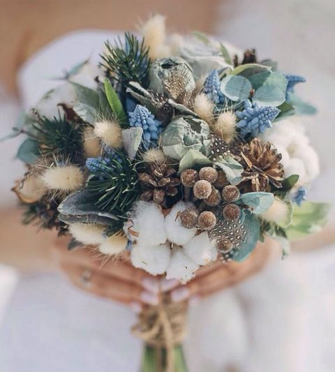 a wedding bouquet with evergreens, pinecones, cotton and berries