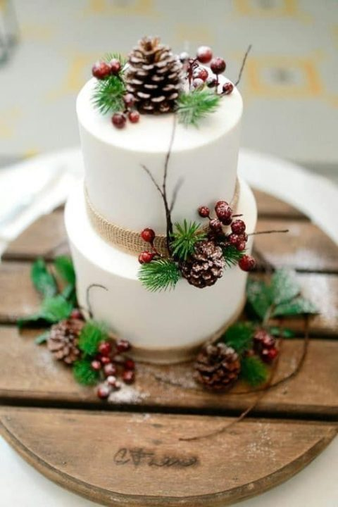 a white wedding cake with berries, burlap, branches and pinecones