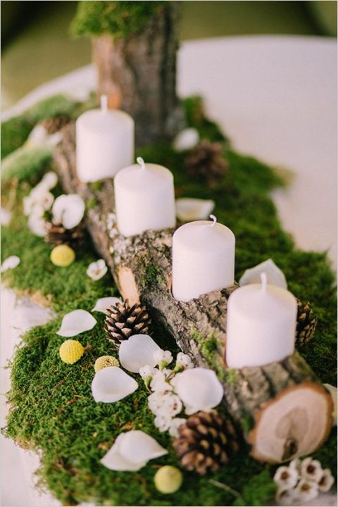 a woodland wedding centerpiece with a log with candles, moss and pinecones