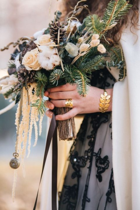 an evergreen and pinecone bouquet with cotton and a vintage pocket watch