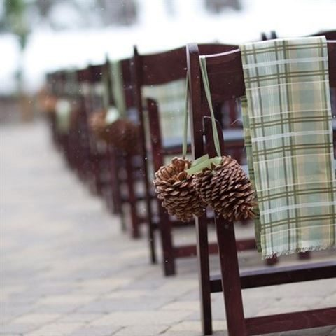large pinecones on green ribbon and green plaid blankets on the chairs